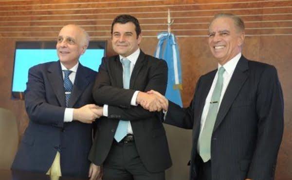 Miguel Galuccio, al centro, estrecha sus manos con los dueños de Bridas, Carlos y Alejandro Bulgheroni. Foto: Télam